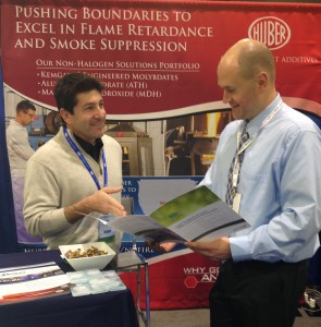 Huber's Omar Mureebe (left) discusses with an IWCS attendee the benefits of Huber's Fire Retardant Additives in Wire & Cable applications.