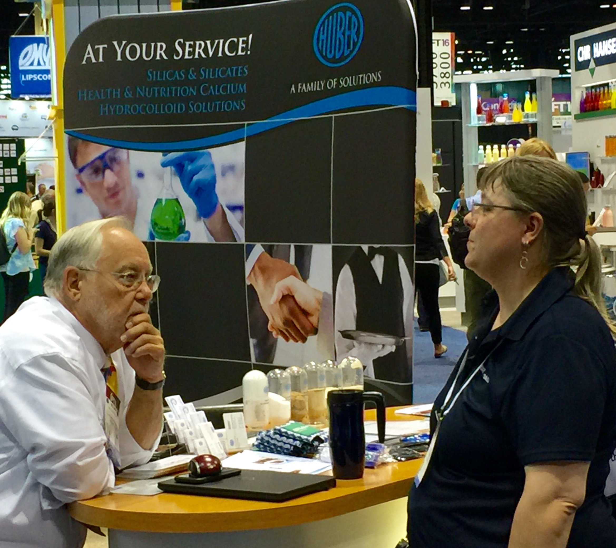 Huber's Sr. Technical Service Representative Nolan Phillps (left) fields questions about Huber's Silicas and Silicates at IFT2016.